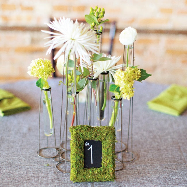 The centerpieces had a unique, vintage look. White and green flowers were arranged in glass vials held in an intricate wire structure. The chalkboard table numbers were framed in earthy moss for a garden-inspired look.