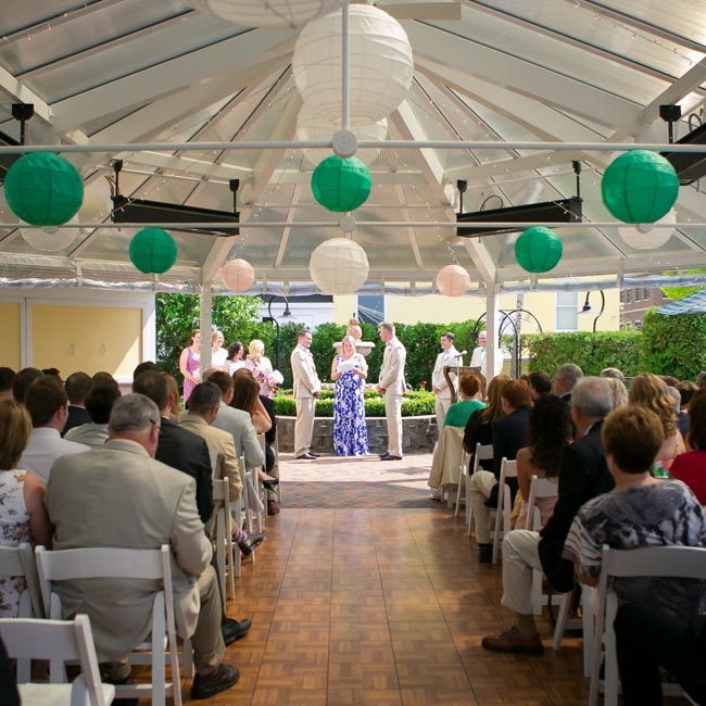 The couple exchanged vows beneath a tent accented with green and white paper lanterns.