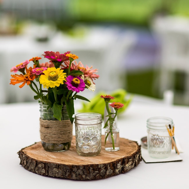 Wooden slabs were topped with Mason jars filled with colorful zinnias at the center of the reception tables.