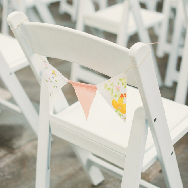 Handmade bunting made from colorful floral fabrics hung from the end chair at each aisle.