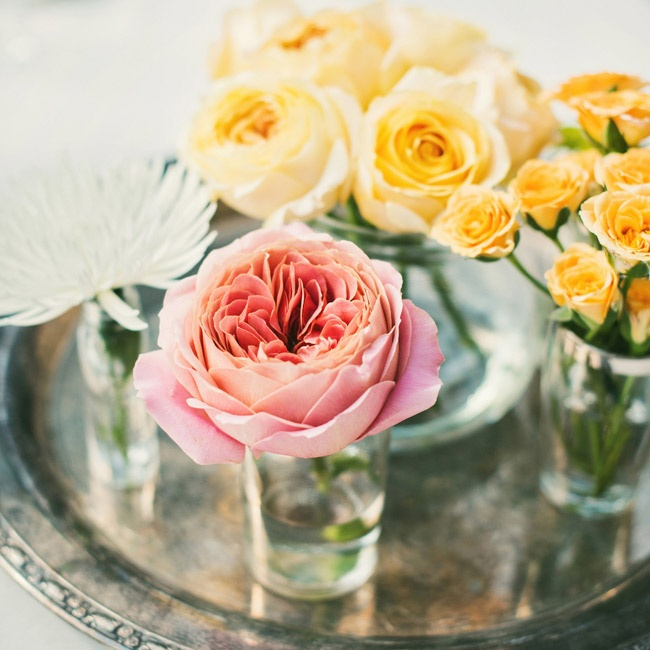 Antique pewter platters were placed at the center of each table and topped with bud vases filled with yellow, pink and white flowers.