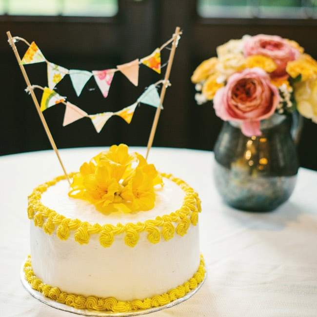 The homemade cutting cake was frosted with white and yellow buttercream and topped with handmade bunting and a fresh bunch of yellow lilies.