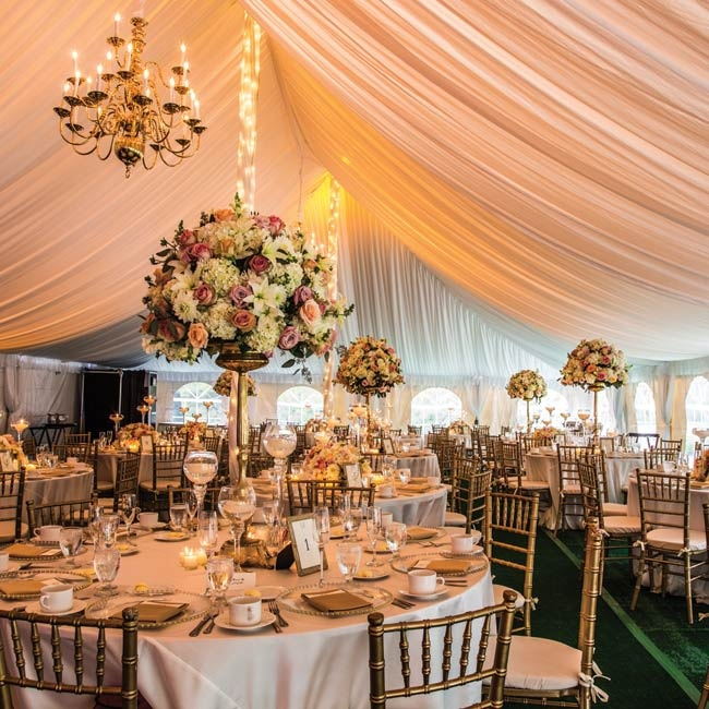 """Because the reception was in a tent, we had to create the entire look from the ground up,"" explains Danielle.  ""We the created a romantic and elegant feel that I wanted with green turf flooring, a wood dance floor, beautiful draping and glowing chandeliers."""