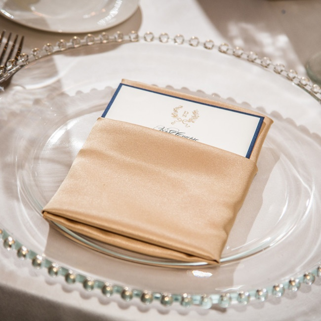 The place settings included a gold-trimmed charger and menus folded within gold satin napkins.