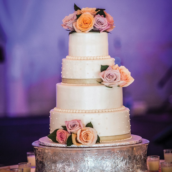 Sean selected all aspects of the four-tiered cake with alternating layers dots and smooth fondant. An airbrush finish, ribbon and pearl borders along with fresh flowers completed the timeless look.