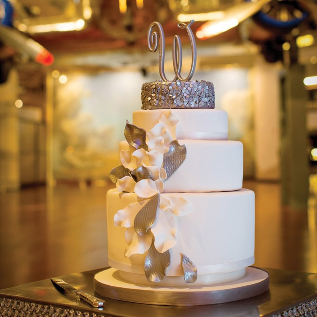 "The couple selected a contemporary white and silver fondant cake with an initial topper. ""The very top layered looked like it was ""rolled"" in silver sequence and there were flower petals bursting out of the middle,"" Tara says."