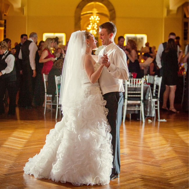 Tara glowed in a dropped waist, Justin Alexander ball gown with an organza ruffle skirt, strapless bodice, sweetheart neckline and flower beading. She had her mother's veil incorporated into an extra two layers of her finger tip veil with sparkle accents.