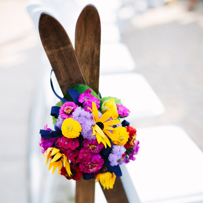 The outdoor aisle was adorned with wooden skis and brightly colored flowers which popped against the white chairs.