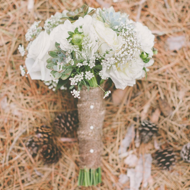 Makenna's bouquet mixed classic white roses with rustic elements like succulents and queen anne's lace. She wrapped the bouquet in burlap ribbon and secured it with three pearl pins.