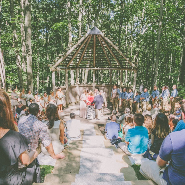 Makenna and Jared gathered with family and friends at the Michigan Legacy Art Park for an intimate woodland ceremony. Guests looked on from unique amphitheater seating as the couple exchanged vows under a log gazebo-like structure.