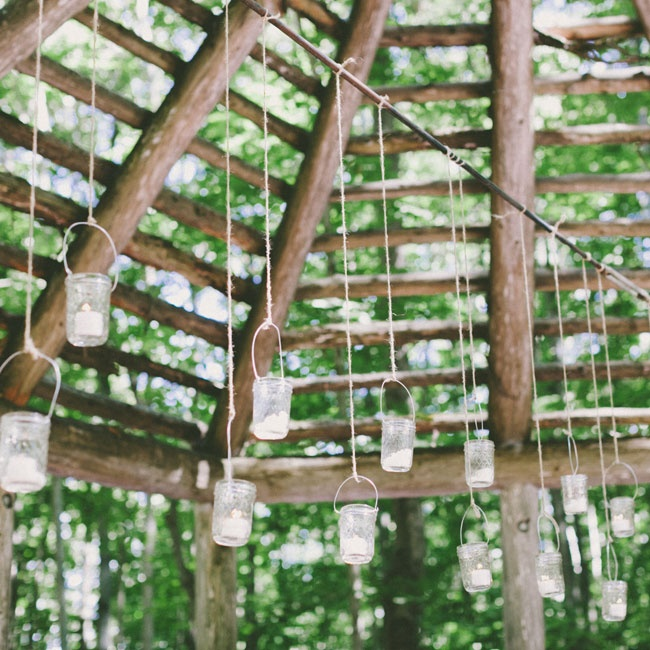 Hanging mason jar lanterns hung from the rafters of the log gazebo adding a whimsical touch to the ceremony decor.