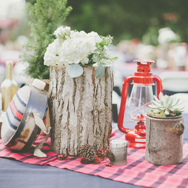 Makenna and Jared decided on a rustic, woodland vibe for their reception decor. They lined the tables with red flannel table runners and centerpieces made from logs, red kerosene lanterns, and unique props like water canteens and miniature pine trees.