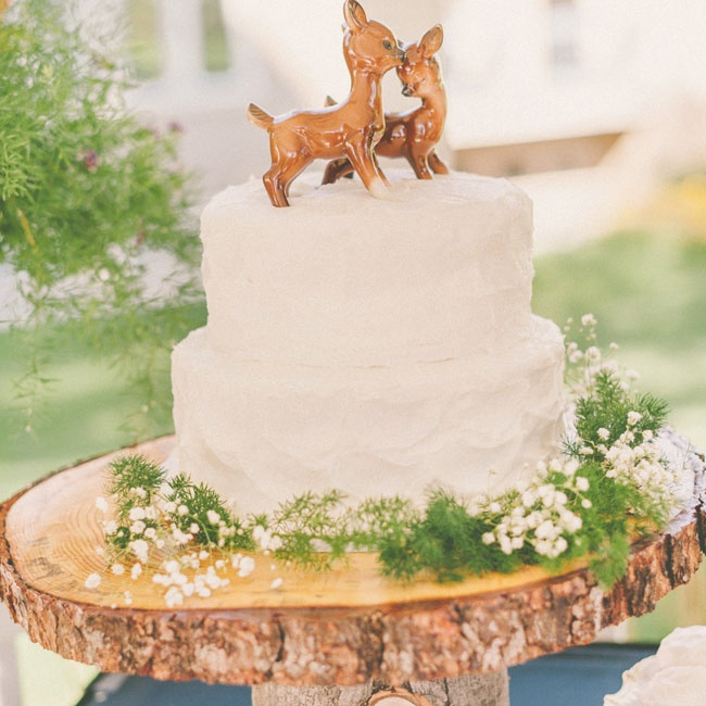 The couple had four cakes in total. Each cake was two tiers with white buttercream frosting and an animal cake topper. The cakes were displayed on log cake stands and were surrounded by baby's breath and sprigs of pine.