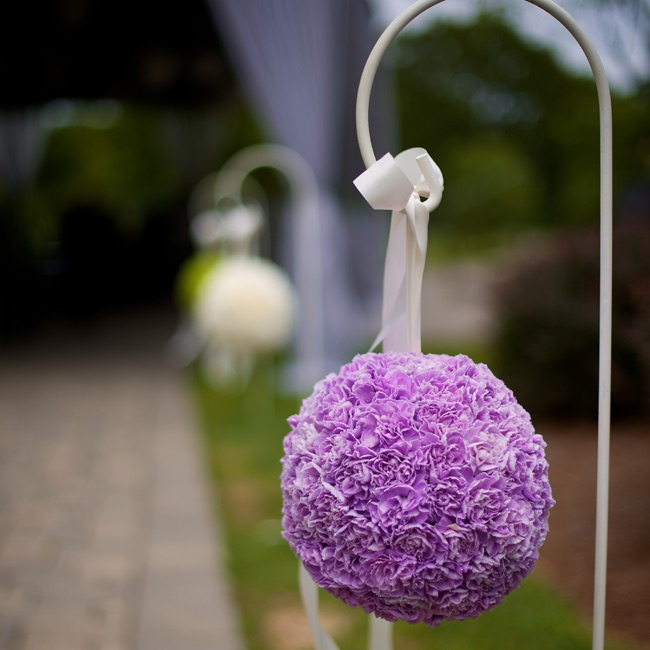 Monochromatic carnation pomanders decorated the outdoor space of Kelly and Ryan's nuptials.