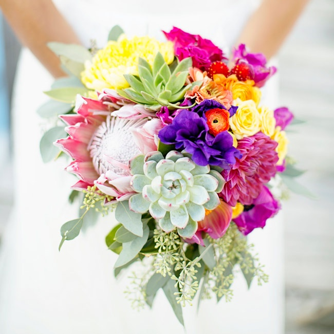 Kendra carried a cheerful bouquet filled with a variety of vibrant blooms including king protea and succulents.