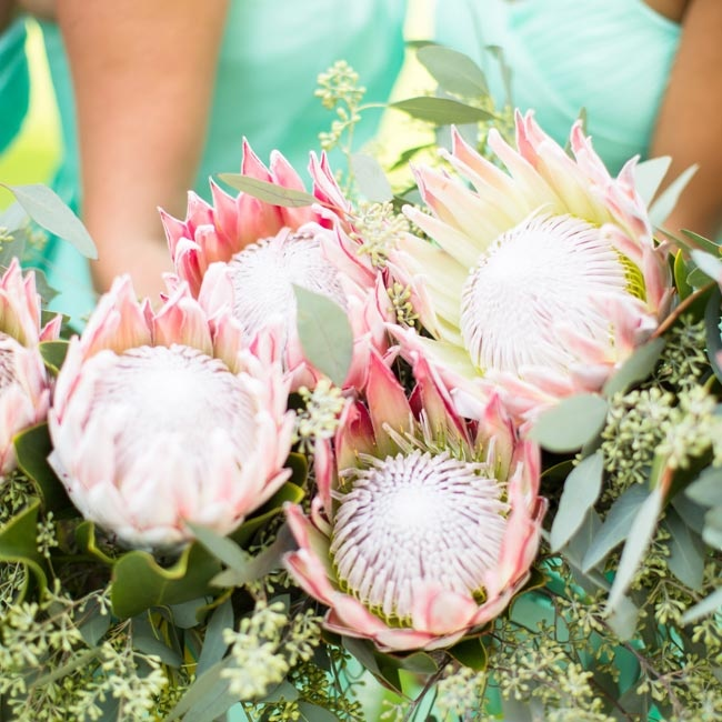 "The bridesmaids carried statement bouquets consisting of a single king protea.  ""I found images of the king protea on pintrest and knew that was what I wanted,"" says Kendra. ""I loved how unique and bold the flower was."""
