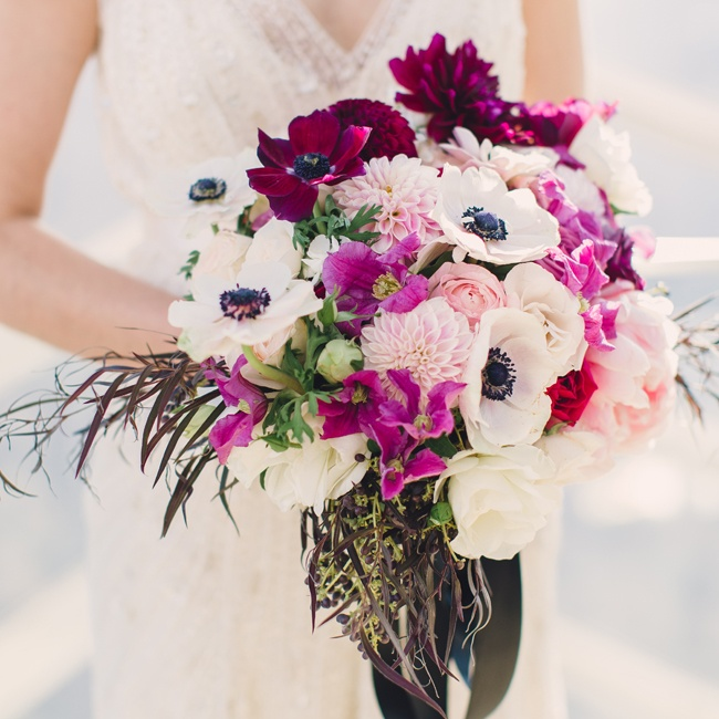 The bride carried a bouquet of deep fuchsia dahlias and white anemones.