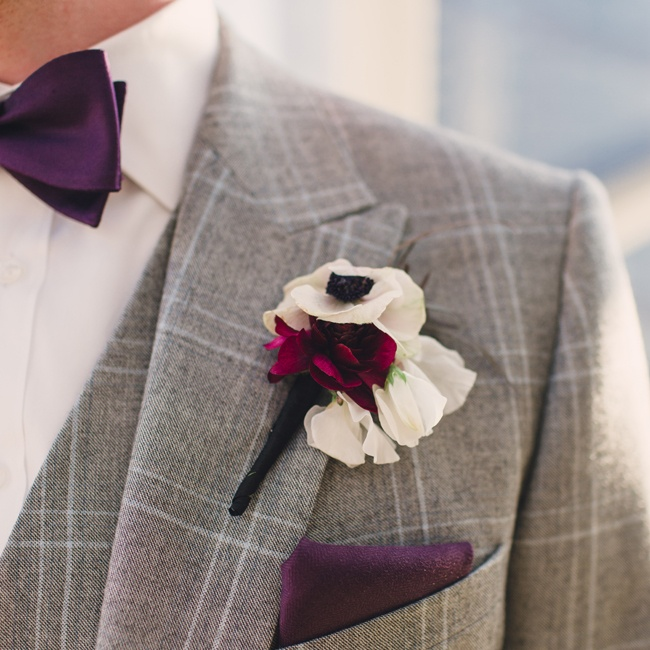 Will accessorized his plaid light gray suit with a dark purple pocket square and bowtie and a fresh anemone boutonniere.