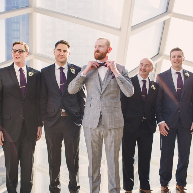 The groom stood out from his groomsmen in his light, plaid suit and bowtie.