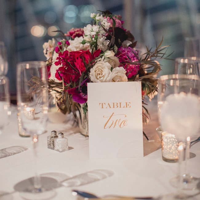 Table numbers were formally spelled out in gold font and laid against lush floral arrangements at the table.