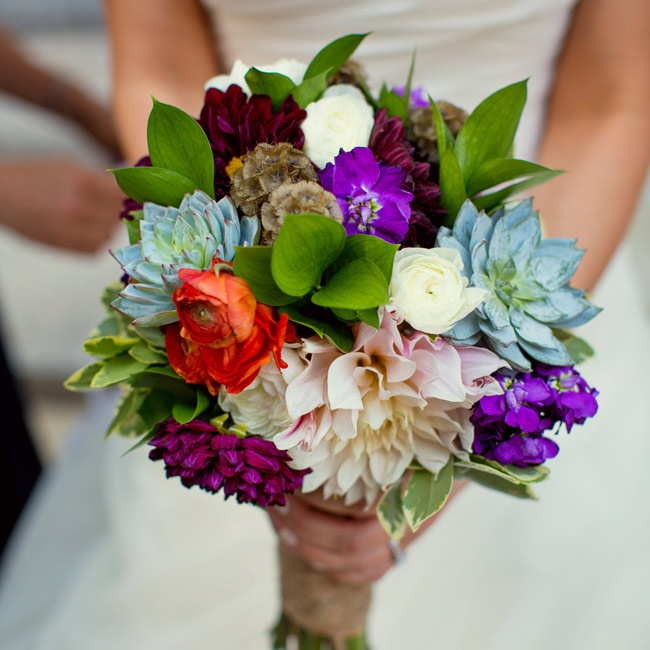 Ashley selected a colorful mix of succulents, dahlias, ranunculus, scabosia pods and textural greens while her bridesmaids carried smaller, complementary bouquets using the same blooms.