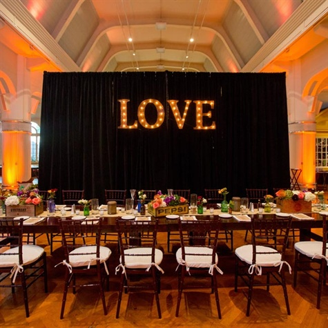 "Ashley and Peter decorated the mahogany farm tables with vintage crates and bottles collected throughout their engagement. ""We absolutely adore the ""LOVE"" light bulb marquee letters that hung behind our head table and it now hangs in our home!"" Ashley says."