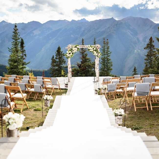 The ceremony was held at the Aspen Wedding Deck overlooking the Maroon Bells and the Rocky Mountains. A white aisle runner was laid over the steps leading down a rustic wedding arch.
