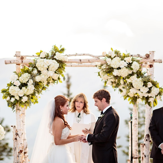 The couple exchanged vows in front of a birch branch wedding arch decorated with lush arrangements of greenery, white roses and hydrangeas. Meredith stunned in a Lazaro gown with a layered, flowing organza skirt and beaded strapless bodice.
