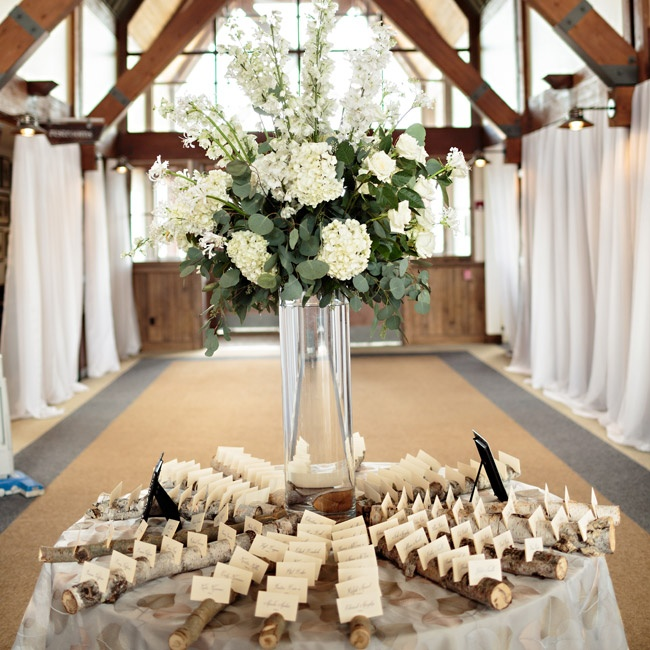 The escort cars were arranged around a tall hurricane vase piled high with hydrangeas, eucalyptus and delphiniums.