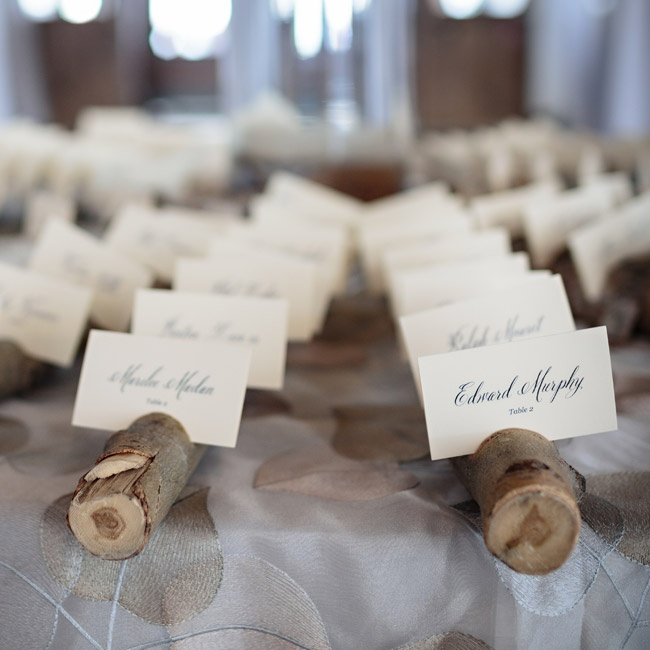 Elegant script escort cards were arranged in sliced tree branches for a unique, rustic look.