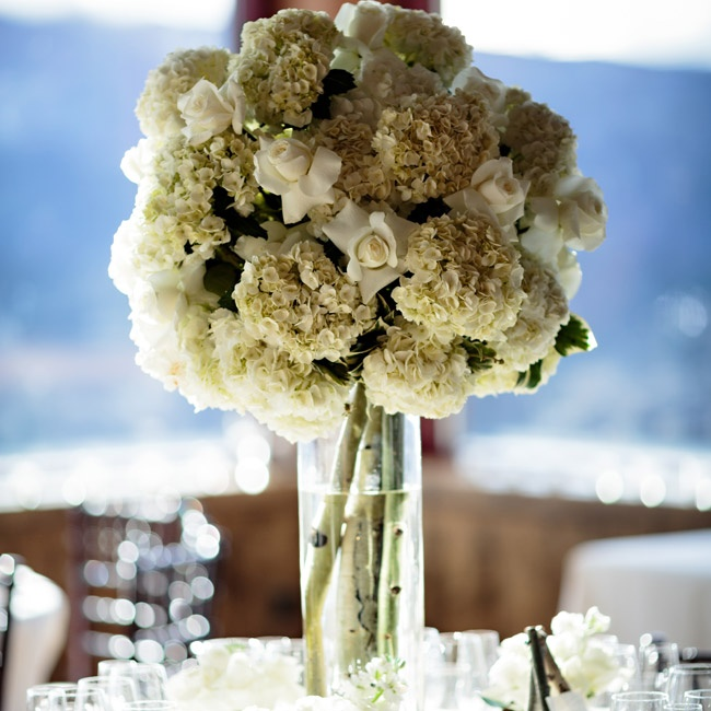 Bunches of hydrangeas and roses were arranged over high hurricane vases filled birch branches.