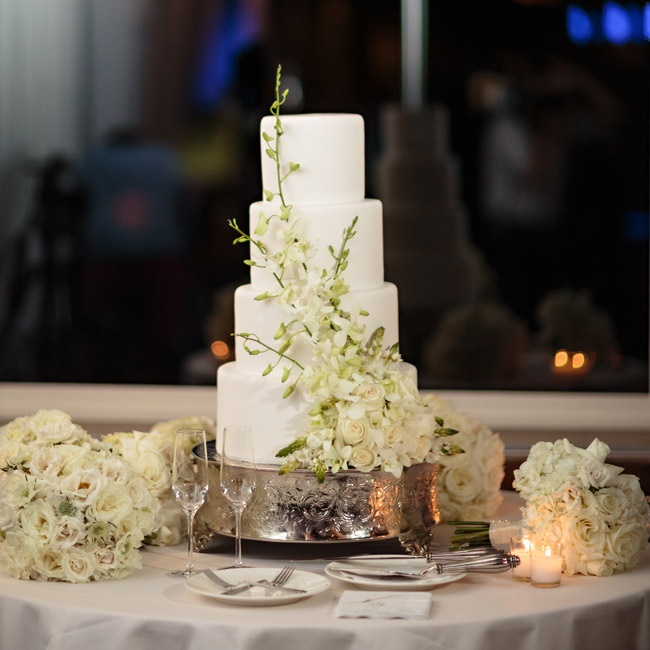 The wedding cake had a simple, sophisticated look with four white fondant-covered tiers accented by a bunch of fresh white delphiniums and roses.