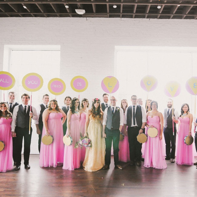 "Instead of flowers, the bridesmaids and groomsmen held gold and teal tambourines and round, hand-painted signs that spelled out ""all you need is love""—a message inspired by The Beatles song of the same name. ""The signs expressed the theme of the night and acted as extra décor. The tambourines, however, were used for a jam session to 'Hey Jude' afte ..."