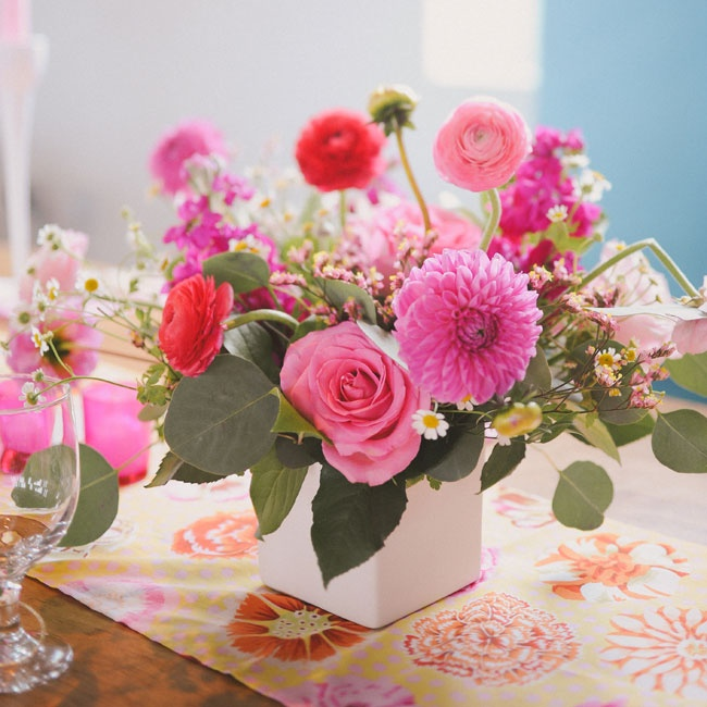 Color blocking inspired the reception decor, with each row of tables featuring a different color scheme of pink, yellow, or purple accents. The centerpiece from the pink table had a charming mix of pink dahlias, roses and ranunculuses.
