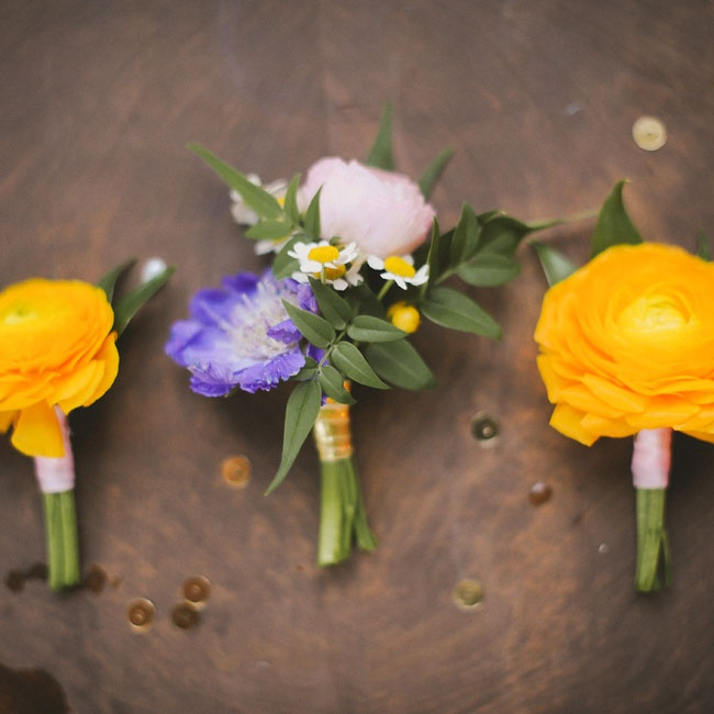 Yellow ranunculus boutonnieres added a pop of color to the groomsmen's lapels.