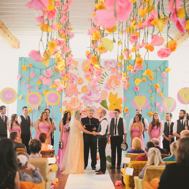 At the ceremony, the aisle led to a giant. hand-painted floral mural by the Stationery Bakery which acted as the altar backdrop. On either side of the mural were aqua walls with cascading paper flower vines flowing over them.