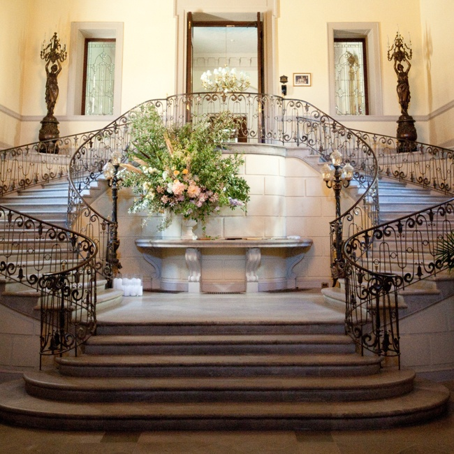 The wedding was held at the grand Oheka Castle on Long Island. Guests were greeted by a grand staircase decorated with lavish pastel blooms before heading into the reception.