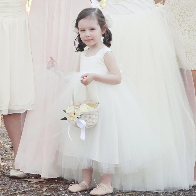 The flower girl wore an ivory dress with a full tulle skirt, blush ballet slippers and her hair pulled back into pigtails.