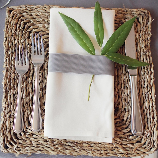 Square, wicker chargers added a chic, rustic touch to each place setting. Simple ivory linens wrapped in gray ribbon and accented with green leaves were placed on each charger.