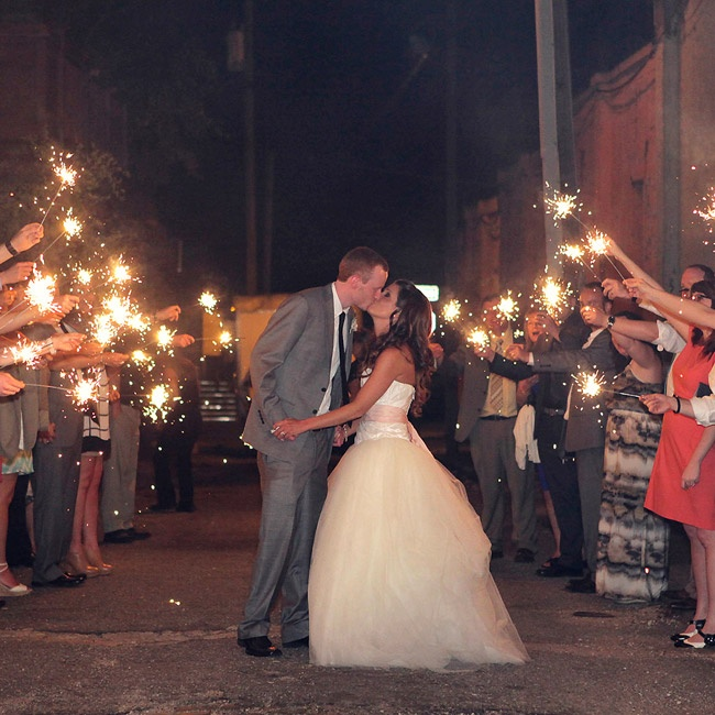 Family and friends sent off the newlyweds with an arch of bright sparklers.