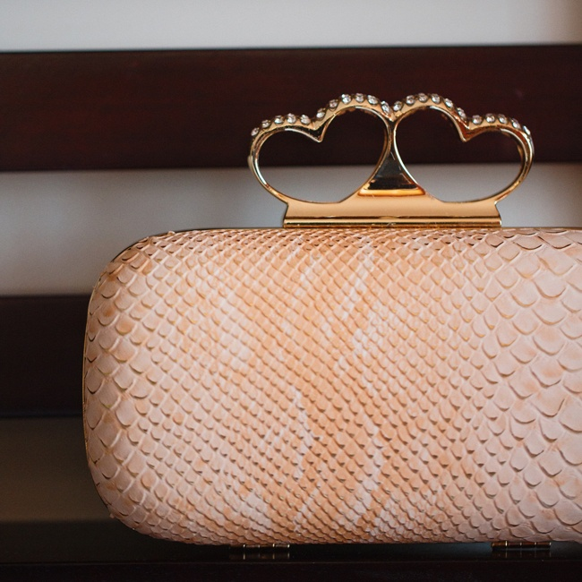 The bride accessorized with a blush colored snakeskin clutch with heart details.