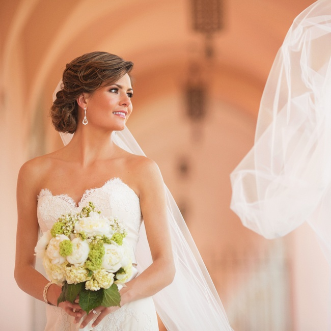 The bride wore her hair in a low, classic updo and fastened a cathedral-length veil to it.