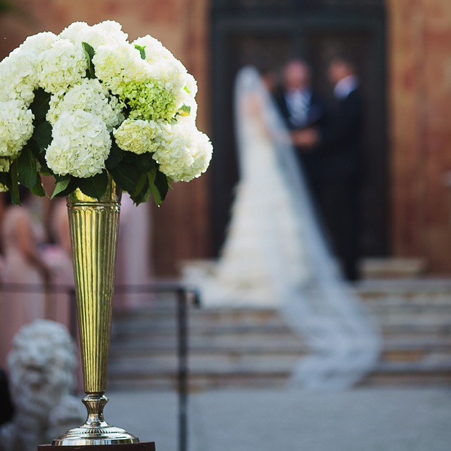 Clusters of white hydrangeas sat in tall metallic vases at the beginning of the ceremony aisle.