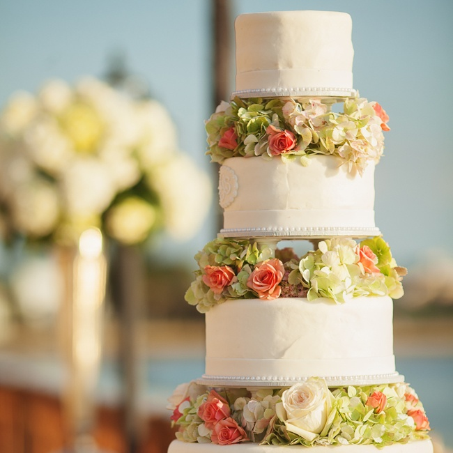 The couple made a statement with their tall cake with layers of green and peach flowers.