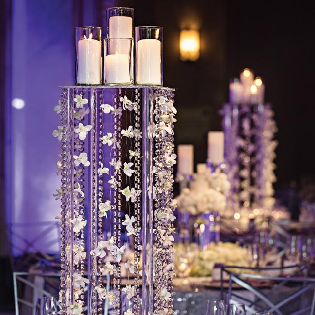 Candles were set on tall rectangular platforms, which were lined with hanging floral garlands and beads.