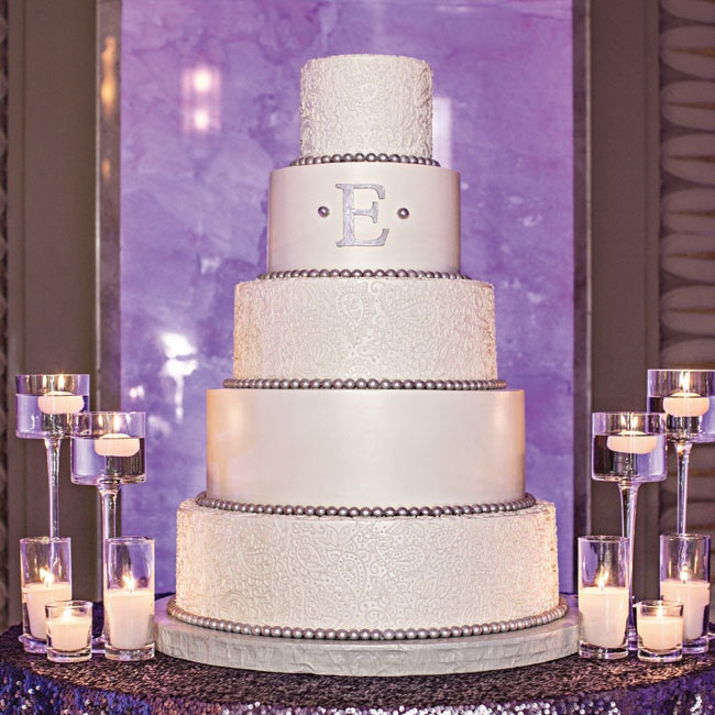 The couple's five-tiered, traditional white wedding cake was embellished with the bride and groom's monogram and alternating lace layers.