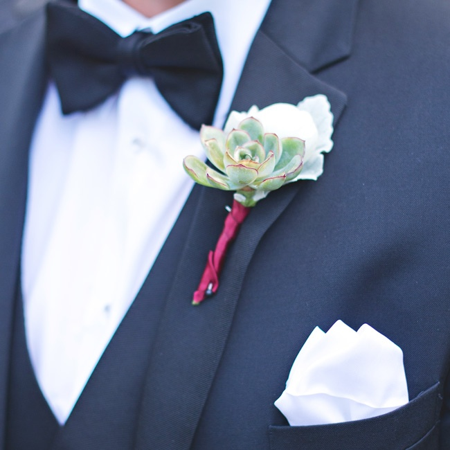Gold-dipped succulent boutonnieres wrapped in burgundy ribbon complemented Elise's bouquet and dress.
