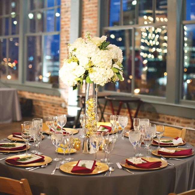 The tables were covered with steel gray tablecloths, gold chargers and burgundy linens that channeled the industrial glam vibe of the wedding. High centerpieces were placed at alternating tables - lush bunches of ivory hydrangeas, roses and stock arranged over hurricane vases filled with light bulbs.