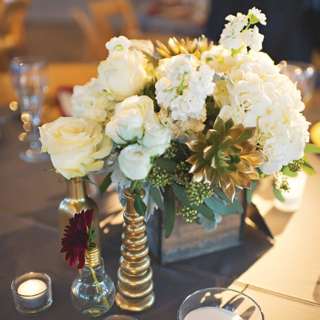 Some of the reception tables were topped with vintage wooden boxes filled with gold-dipped succulents, ivory hydrangea, stock and roses for a rustic look. Gold-painted and light bulb bud vases were scattered along side the centerpieces, adding a unique touch to the tablscapes.