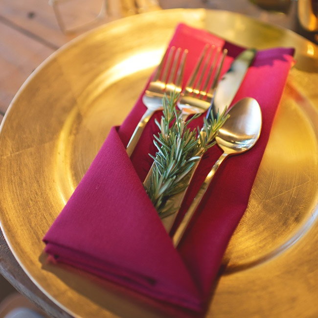 Gold tone flatware and sprigs of fresh rosemary were tucked into burgundy linens and placed on gold chargers.